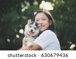 Stock photo beautiful asian girl playing with siberian husky puppy in the park with bokeh background 630679436