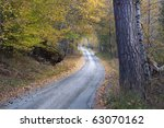 Narrow country road in autumn - stock photo