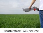 Man holds fixed wings drone while standing in a wheat field, prepares for drone launch and aerial imaging of crops. Left wing visible.