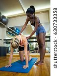trainer assisting a woman while ... | Shutterstock . vector #630733358