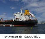 Small photo of Products Tanker discharging at the Oil Terminal of Lorient, France, with black hull and yellow funnel on a sunny day. Horizontal view of the aft part.
