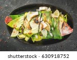 Small photo of Gish. seafood. Asian and Eastern cuisine. Red tilapia roasted on a grill in leaves of leeks with slices of lime, herbs and spices. In the frying pan, grill. Top view copy space