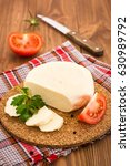 Small photo of Sliced Adyghe cheese, tomato and parsley on a substrate on a wooden table