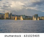 Small photo of Honolulu, Hawaii, USA, May 1, 2017: Offshore sunset view of sailboats in Waikiki with Oahu and a cloudy sky in the backdrop.