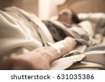 Small photo of Sick in bed. Woman in hospital bed with iv on her arm.