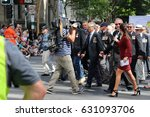 Small photo of BRISBANE, AUSTRALIA - APRIL 25, 2017: TV reporter walks alongside army veterans during the ANZAC parade.