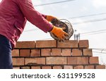 worker builds a brick wall in... | Shutterstock . vector #631199528
