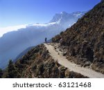 A lone trekker walks along a perfect mountain trail in the Himalaya, Nepal - stock photo
