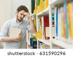 Small photo of Handsome young tired man rubbing his forehead looking exhausted and stressed while preparing for his exams at the library copyspace education knowledge expressive emotional headache aching concept
