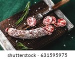 dried sausage on a wooden board ... | Shutterstock . vector #631595975