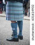 Small photo of closeup of men legs with scottish kilt in the street