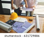 blueprint on wooden desk with... | Shutterstock . vector #631729886