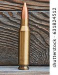 Small photo of Full metal jacket bullet on wooden background