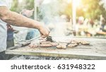 man cooking meat at dinner... | Shutterstock . vector #631948322