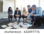 Small photo of Business team brainstorming in office, crouching to look at assorted ideas on floor