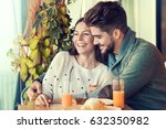 young couple sitting in cafe by ... | Shutterstock . vector #632350982