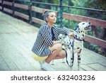 Stock photo woman pretty girl on the bridge holding her dog who is barking to strangers 632403236