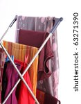 Small photo of colorful clothes hanged for drying after laundry clothes airer, clothes dryer isolated on white