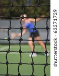 Tennis net with player returning serve in the background - stock photo