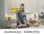 young woman flattening a dough... | Shutterstock . vector #632821922