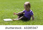 child sitting on meadow with closed laptop - stock photo
