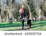 Stock photo beautiful blonde walks in the park with her dog breeds a rottweiler holds her by the collar 633035726