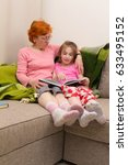 Small photo of Grandmother and grandchild read book, they are sitting on couch and plaid, girl holding book and read it aloud and smile