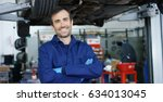 Small photo of Portrait of a young beautiful car mechanic in a car workshop, in the background of service. Concept: repair of machines, fault diagnosis, repair specialist, technical maintenance and on-board computer