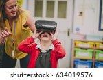 teacher is helping one of her...   Shutterstock . vector #634019576