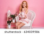 Stock photo fashion photo of a beautiful elegant young woman in a pretty dress with flowers holding handbag 634039586
