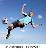 Male football player kicking the ball in the air - stock photo
