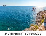 a boy is jumping from the cliff.... | Shutterstock . vector #634103288