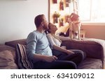 Stock photo beautiful couple relaxing at home and loving their pet 634109012
