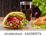 Sandwich with pulled pork and glass of cola on stone table