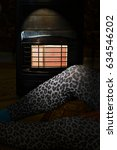 Small photo of A lady sitting on a carpet near a gas heater in the dark with window light in a cold night and power failure in the house
