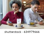 Small photo of Closeup of dark skinned female and European female sitting in cafe together but experiencing problems in relationship, each staring at their own smartphone, looking tired, puzzled and frustrated.