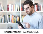 man holding an e book reader in ...   Shutterstock . vector #635030666