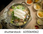 Small photo of Top view of friends eating korean seafood hotpot and Kimchi
