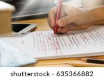 hand holding red pen over... | Shutterstock . vector #635366882