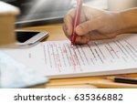 hand holding red pen over...   Shutterstock . vector #635366882