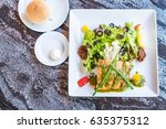grilled salmon steak with salad | Shutterstock . vector #635375312