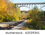A passenger train rounds a curve and approaches under a high arch bridge in a scenic area - stock photo