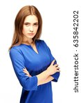 Small photo of A strict young girl crossed her arms over her chest. Wicked woman in a blue dress. Beautiful and inaccessible model. Studio portrait of a serious teacher. Graduate of high school.