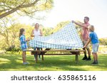 family spreading the tablecloth ... | Shutterstock . vector #635865116