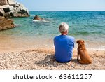 Stock photo elderly man with his dog at the summer beach 63611257