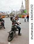 Small photo of MOSCOW, RUSSIA - MAY 06, 2017: A motorcycle driver reads a brochure in parking against the background of buildings, pr. Academician Sakharov. Motofestival 2017