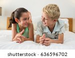 smiling siblings lying on bed... | Shutterstock . vector #636596702