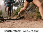 Healthy young couple running on mountain trail in morning. Young man and woman jogging on country path, focus on legs.