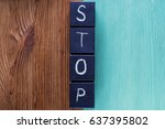 Small photo of Concept of word Stop, contradistinction or versus. Word STOP on wooden cubes separates and contrasts the wooden background. Two-colored wooden background, antonym concept.