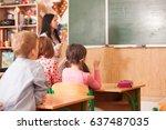 teacher helping pupil at... | Shutterstock . vector #637487035